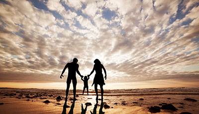 Happy family together hand in hand on the beach at sunset. Summe